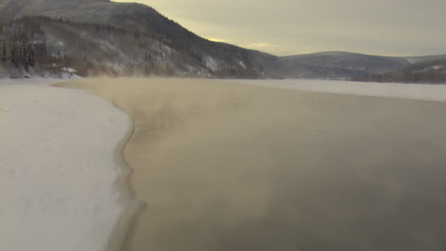 A thin crust of ice covers the edges of the Yukon River in Canada.