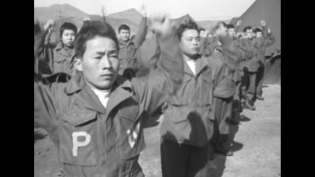 thin prisoner dons coat with aid of helmeted american / large group of north koreans perform calisthenics with individual faces of men during workout... - thin stock videos & royalty-free footage