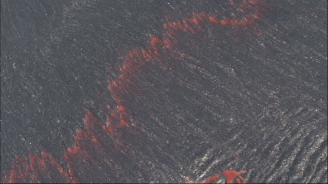 A thin surface of molten lava flows and splits. Available in HD.