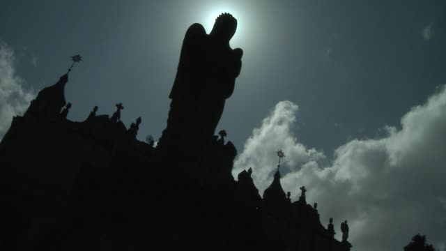 thin, white clouds pass over silhouette of an angel outside a church in addis ababa, ethiopia. available in hd. - church stock videos & royalty-free footage