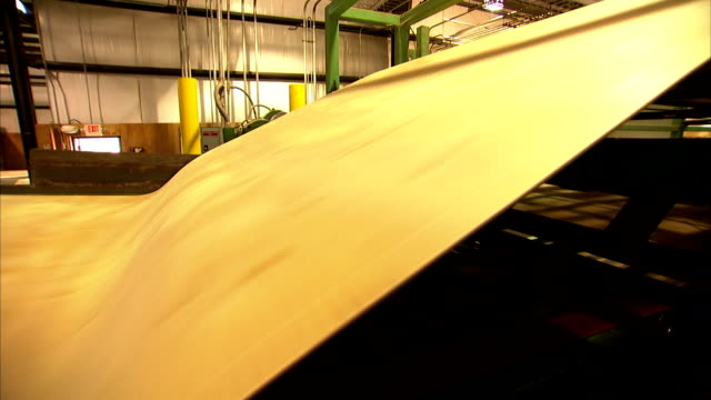 vídeos de stock e filmes b-roll de thin, wide sheets of wood are ejected from machinery. - magro