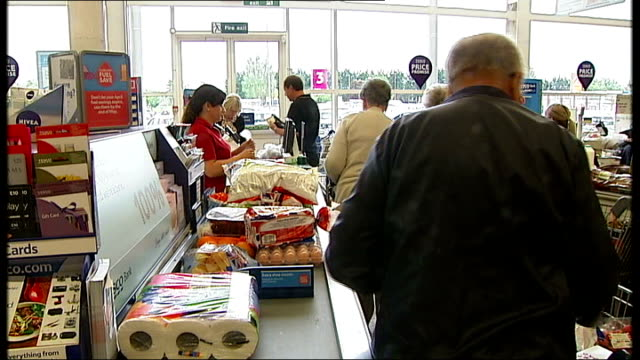 Think tank blames lack of exercise for obesity crisis T22051424 Customers queuing at checkouts in Tesco supermarket Location unknown Hand picking up...