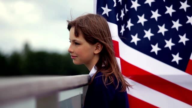 彼女の背後にアメリカの国旗で 10 代の少女を考えてください。 - 市民点の映像素材/bロール