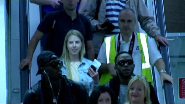 third day of competition; scotland: g;asgow: int usain bolt down escalator as arrives at airport, followed by man playing 'scotland the brave' on the... - 後を追う点の映像素材/bロール