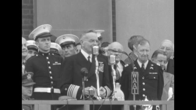 Third Fleet Commander Admiral William Bull Halsey speaks into microphones from balcony one mike is from WAAT several other officers and civilian VIPs...