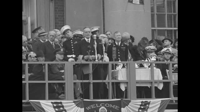 Third Fleet Commander Admiral William Bull Halsey speaks into mikes from balcony one mike is from WAAT several other officers and civilian VIPs on...