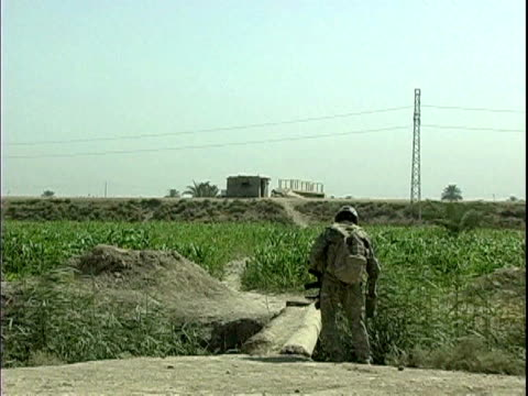 third infantry division us soldier searching for land mines in field / arab jabour, iraq / audio - searching点の映像素材/bロール