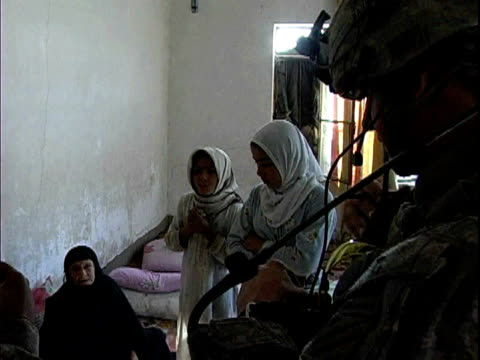 third infantry division us soldiers talking to girls in their home / arab jabour iraq / audio - 言語翻訳点の映像素材/bロール