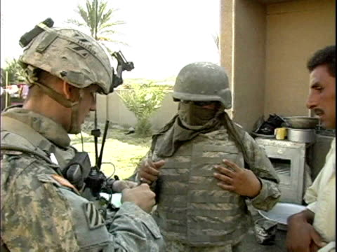 third infantry division us soldiers talking to iraqi man while his family sits nearby / arab jabour, iraq / audio - 2007 bildbanksvideor och videomaterial från bakom kulisserna