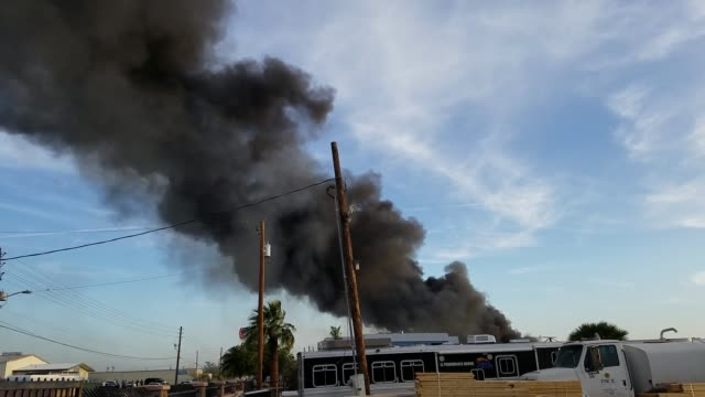 third-alarm fire in phoenix at the arizona pacific pulp and paper recycling plant, near sky harbor airport. - fire protection suit stock videos & royalty-free footage