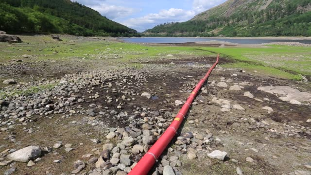 thirlmere reservoir which is drying up rapidly due to the ongoing dry weather leading united utilities to introduce a hosepipe ban. july 2018, with an underwater electric cable refealed by the drought. - reservoir stock videos and b-roll footage