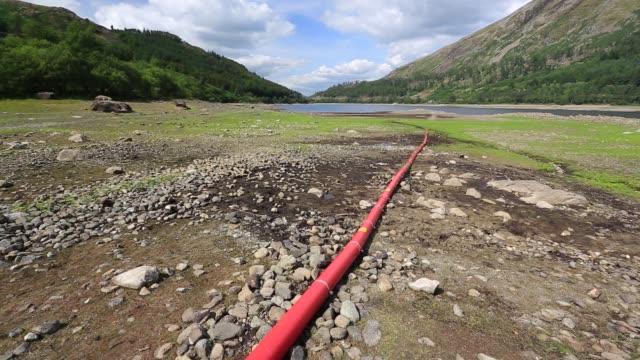 thirlmere reservoir which is drying up rapidly due to the ongoing dry weather leading united utilities to introduce a hosepipe ban. july 2018, with an underwater electric cable refealed by the drought. - northwest england stock videos and b-roll footage