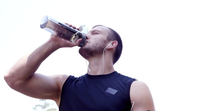 Thirsty and exhausted athlete drinking water after workout, slow motion