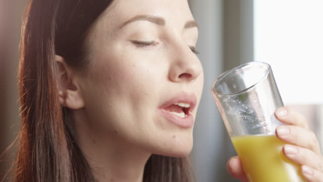 thirsty woman drinking orange juice indoors with sun shining a close up shot on red camera - juice drink stock videos & royalty-free footage