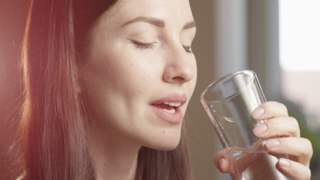 vidéos et rushes de thirsty woman drinking water from a glass indoors with sun shining a close up shot on red camera - verre d'eau