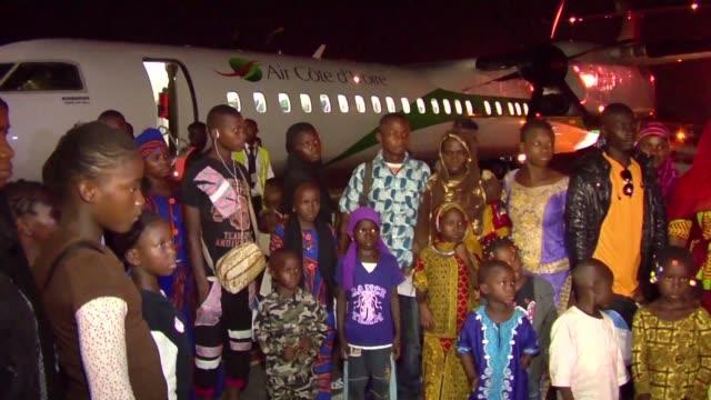 stockvideo's en b-roll-footage met thirty five ivorian refugees repatriated voluntarily from guinea arrive at abidjan airport - repatriëring