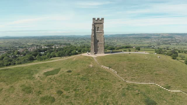 this 4k stock footage clip shows an aerial view of the glastonbury tor & st michael's tower, an ancient monument steeped in legend and mythology atop... - rock formation stock videos & royalty-free footage