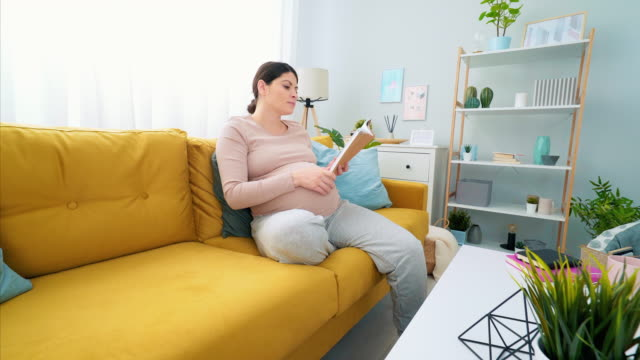 dieses buch beantwortet alle meine schwangerschaftsfragen. - single mother stock-videos und b-roll-filmmaterial