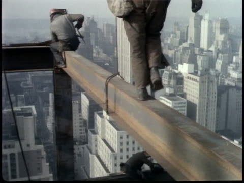this clip is a hand-held mls of workers doing various things as they walk and sit on a girder high above the streets of manhattan. - sport stock videos & royalty-free footage