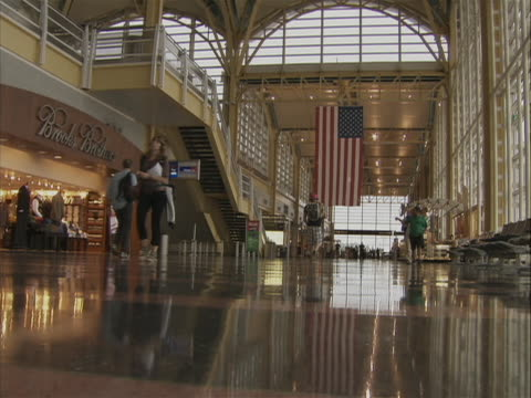 this clip is a low angle a terminal at ronald reagan washington airport. you can see people walking through out the terminal and a american flag... - flughafen washington ronald reagan national stock-videos und b-roll-filmmaterial
