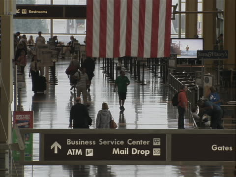this clip is a terminal in ronald reagan washington national airport. you can see the bottom of an american flag and a sign that reads business... - flughafen washington ronald reagan national stock-videos und b-roll-filmmaterial