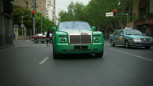 this clip is mute. clean: exterior shots of a green coloured rolls royce phantom drophead coupe being driven on the streets of shanghai. british cars... - ロールスロイス点の映像素材/bロール