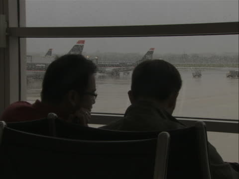 this clip starts off as a a jet sitting on tarmac in the rain as see from the waiting area of airport terminal. the camera than zooms out and you can... - flughafen washington ronald reagan national stock-videos und b-roll-filmmaterial