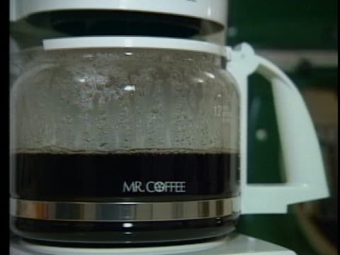 this clip starts out with an up close shot of a coffee pot making coffee the mr coffee logo is clearly in frame then the camera zooms out to reveal... - coffee pot stock videos & royalty-free footage