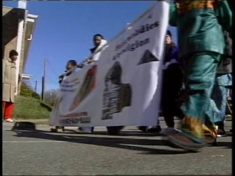 this clips first shot is a group of people holding a banner that says kwanzaa on it marching in a parade. the second shot is a low angle shot of a... - african american culture stock videos & royalty-free footage