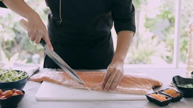 so schneiden sie die lachshaut. - küchenmesser stock-videos und b-roll-filmmaterial
