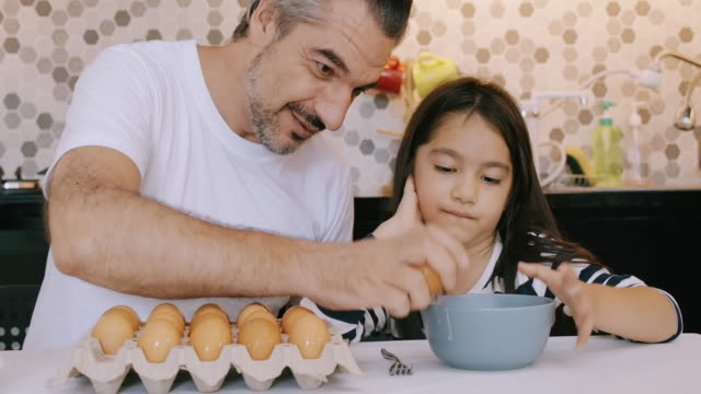 vídeos de stock e filmes b-roll de this is how you pop an egg. - domestic kitchen