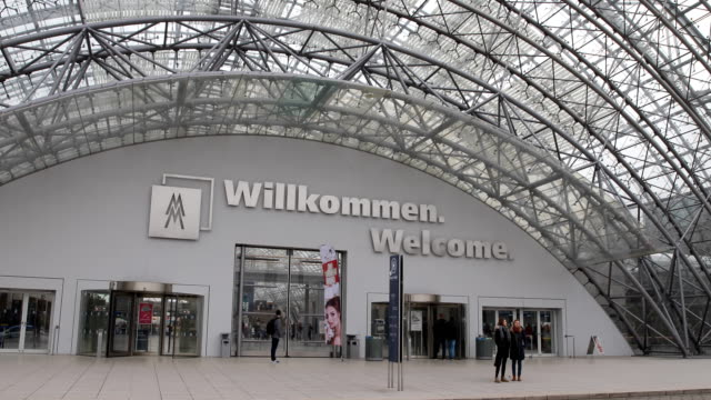 this is the huge glass hall and main entrance hall between the leipzig trade fair buildings, visitors are passing by. - exhibition stock videos & royalty-free footage