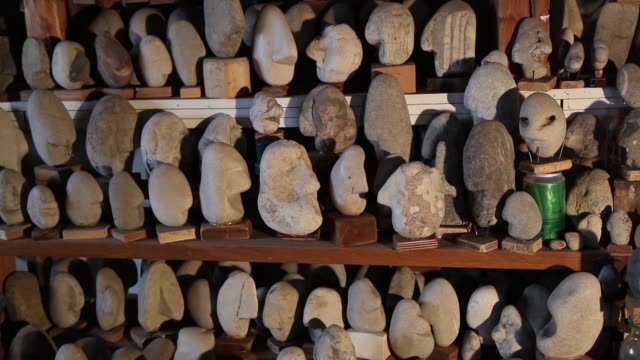 this shot shows a shelved display of uniquely shaped stones all shaped in a way that resembles the side of a human's face. the shot zooms out three... - human face video stock e b–roll
