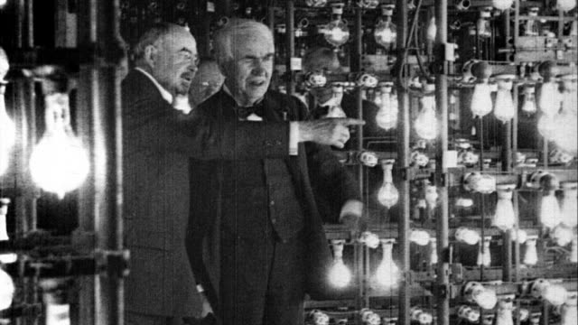 vídeos de stock, filmes e b-roll de thomas edison and men walk through lamp testing area of general electric plant and look at many lamps being tested thomas edison visiting general... - 1923