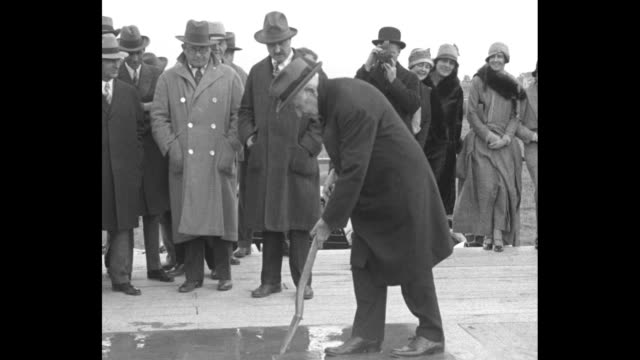 thomas edison climbs stairs to platform, walks to spot and plunges spade into wet cement, dignitaries wearing hats and overcoats stand on platform /... - ヘンリー・フォード点の映像素材/bロール