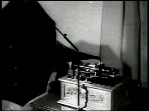 stockvideo's en b-roll-footage met 'talking machine' ms thomas edison cylinder phonograph dramatization int vs couple in early 20th century clothing in living room parlor w/ phonograph... - 1949