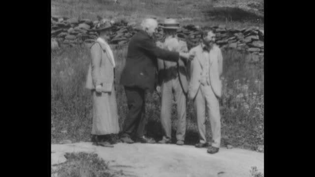 ws thomas edison john burroughs and harvey firestone stand with woman and chat as edison points / cu burroughs edison and firestone sit in front of a... - 発明家点の映像素材/bロール