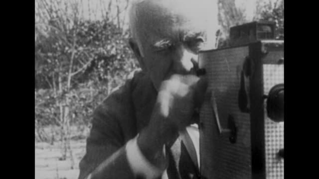 thomas edison, outdoors, peers through hand-cranked camera, turns crank / edison's friend, industrialist henry ford, sitting in a chair outdoors /... - 撮影機材点の映像素材/bロール