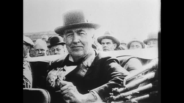 CU Thomas Edison sitting in car holding flower / Edison driving along in car with wife and Mr and Mrs Harvey Firestone
