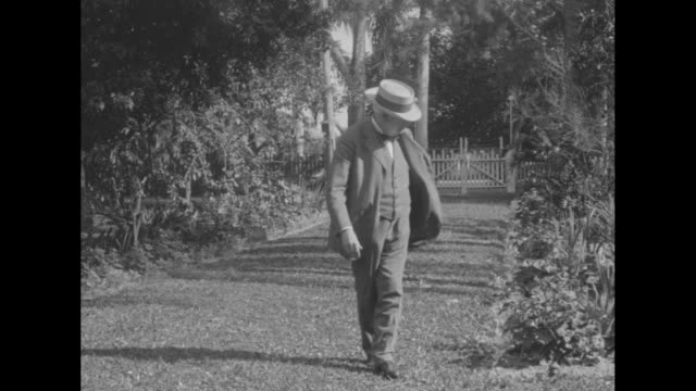 vídeos y material grabado en eventos de stock de cu thomas edison sitting on wicker chair on front porch / edison walks through yard and stops and looks at plant in garden gate behind him / edison... - fort myer