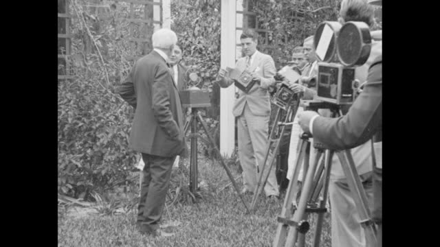 thomas edison standing in front of trellis / edison salutes photographer and cameraman who are shooting him / row of cameramen with movie cameras and... - newsreel stock videos & royalty-free footage