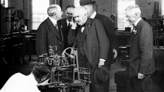 vídeos de stock, filmes e b-roll de thomas edison touring general electric / edison leaning in to hear man speaking / man working on machine for automating manufacturing process / men... - 1923