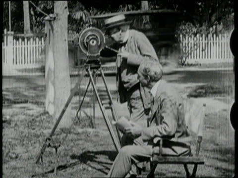 Thomas Edison turns the lever on a film camera as Henry Ford watches