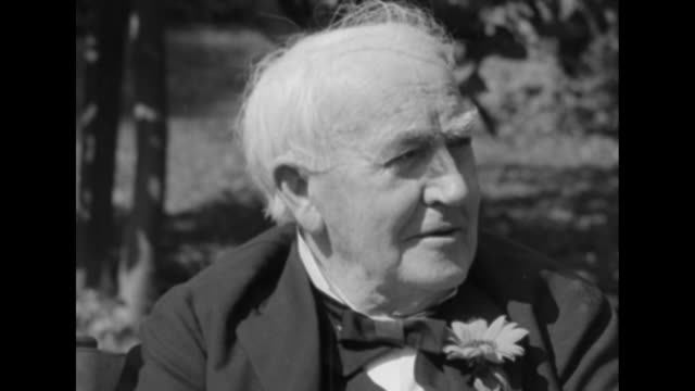 CU Thomas Edison wearing a daisy in his lapel smiles looks at camera as he sits in the garden of his winter home in FL on his 84th birthday