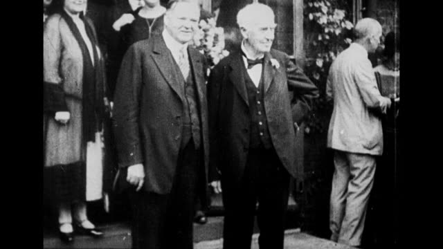 CU Thomas Edison wearing Homburg hat smiles as he stands outdoors / 2shot Edison with Pres Herbert Hoover at event they shake hands outside building...