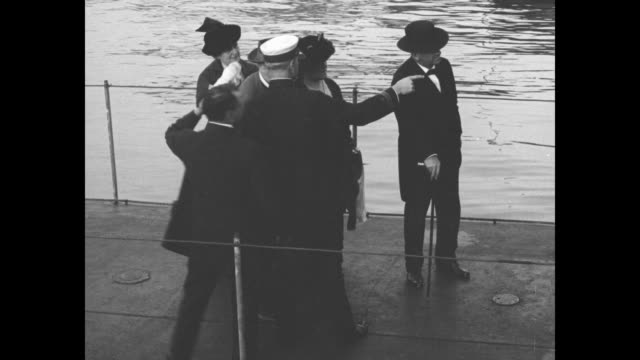 Thomas Edison wife Mina Mrs Josephus Daniels and War Secretary Josephus Daniels with uniformed men standing on a deck of a ship / pan the group poses...