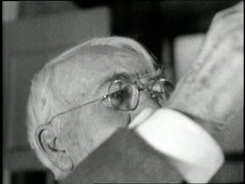 Thomas Edison works in his laboratory and removes his eyeglasses for cleaning