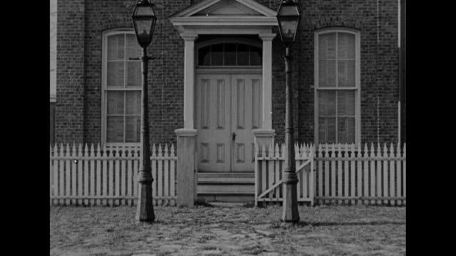 ws thomas edison's menlo park library and office / entrance to the building with streetlamps and white picket fence / man rides horsedrawn wagon past... - cocchio video stock e b–roll