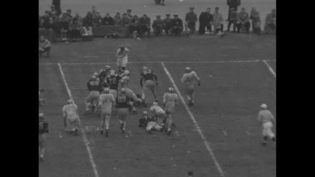thomas forrestal, navy midshipmen quarterback, drops back and throws interception to david bourland, army black knights quarterback, who is tackled... - 士官候補生点の映像素材/bロール