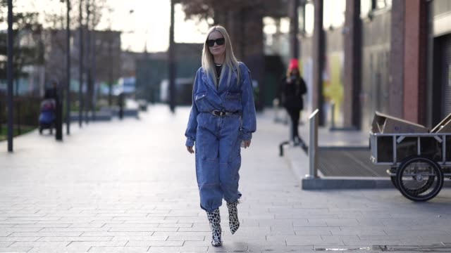 thora valdimars wears sunglasses a blue denim oversized jacket a belt blue jeans black and white cow pattern printed high heeled boots during london... - jeans stock videos & royalty-free footage